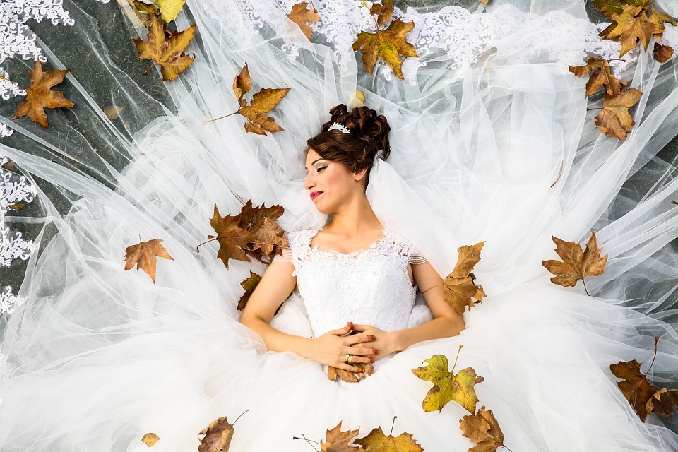 bride surrounded by autumn leaves